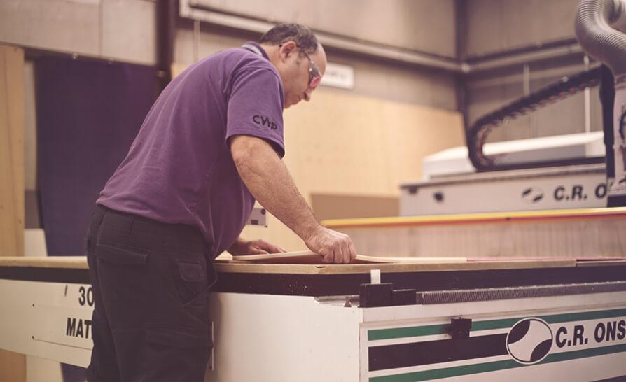 man cutting wood with a machine